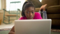 African American female teen on floor with laptop