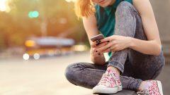 Empowered girl blogging from cellphone in Omaha, NE