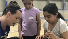 woman working with two young girls at FITGirl workshops in Omaha, NE